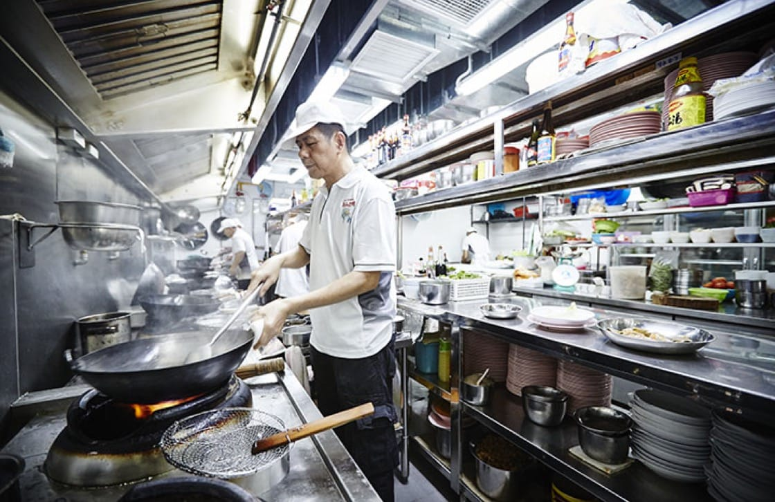 Owner Wang Feng working on a dish. Photography by Wong Weiliang.