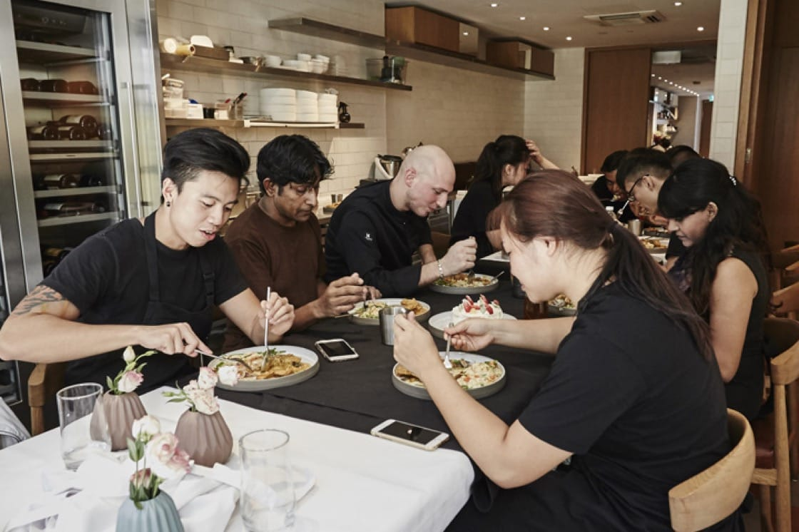 The staff of The Kitchen at Bacchanalia sitting together for a meal. Photography by Wong Weiliang.