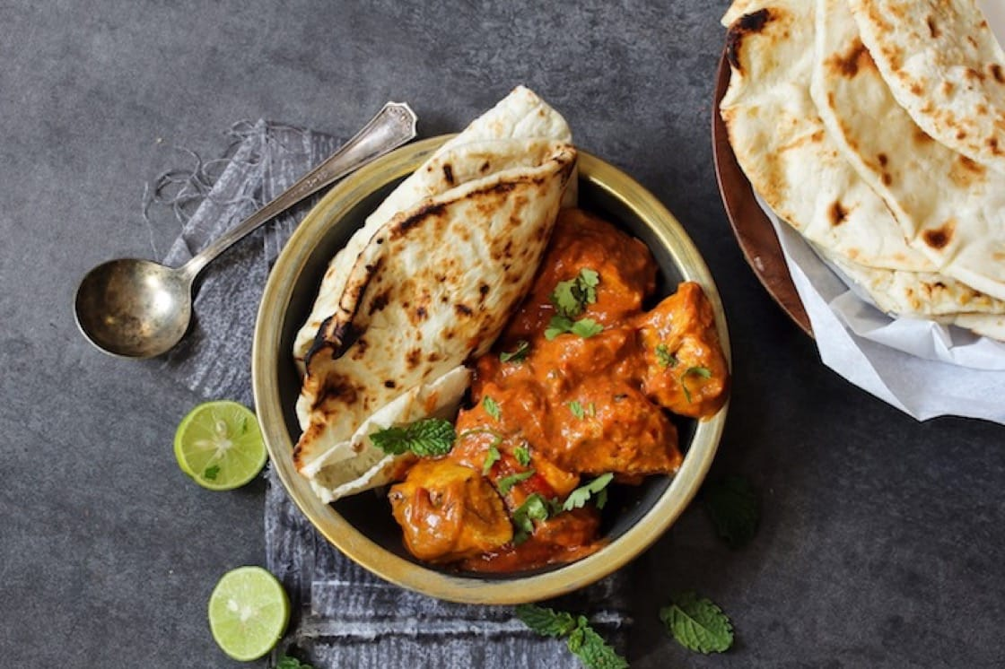 Doughy naan accompanied by a bowl of butter chicken