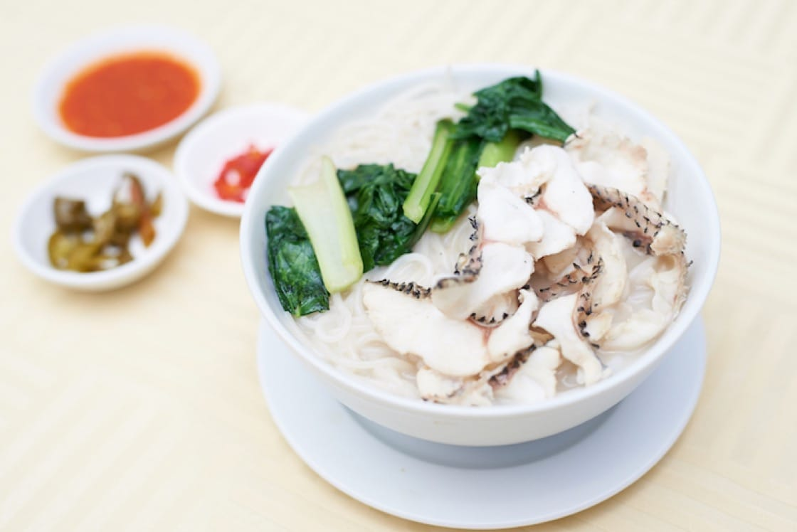 Rich, tasty sliced fish soup from Ka Soh served with cut bird's eye chilis and cubes of fried lard