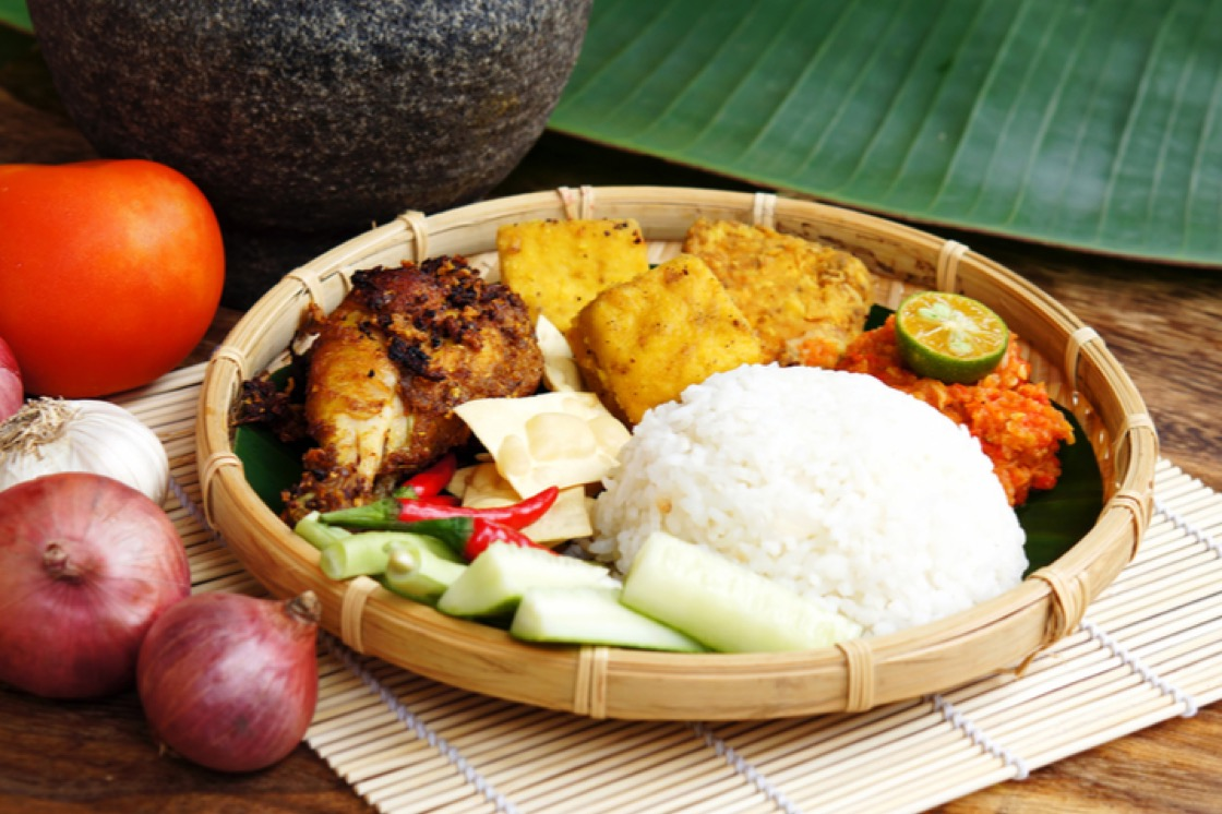 Ayam Penyet is gently crushed in a mortar and pestle or metal hammer, which makes the meat more tender.
