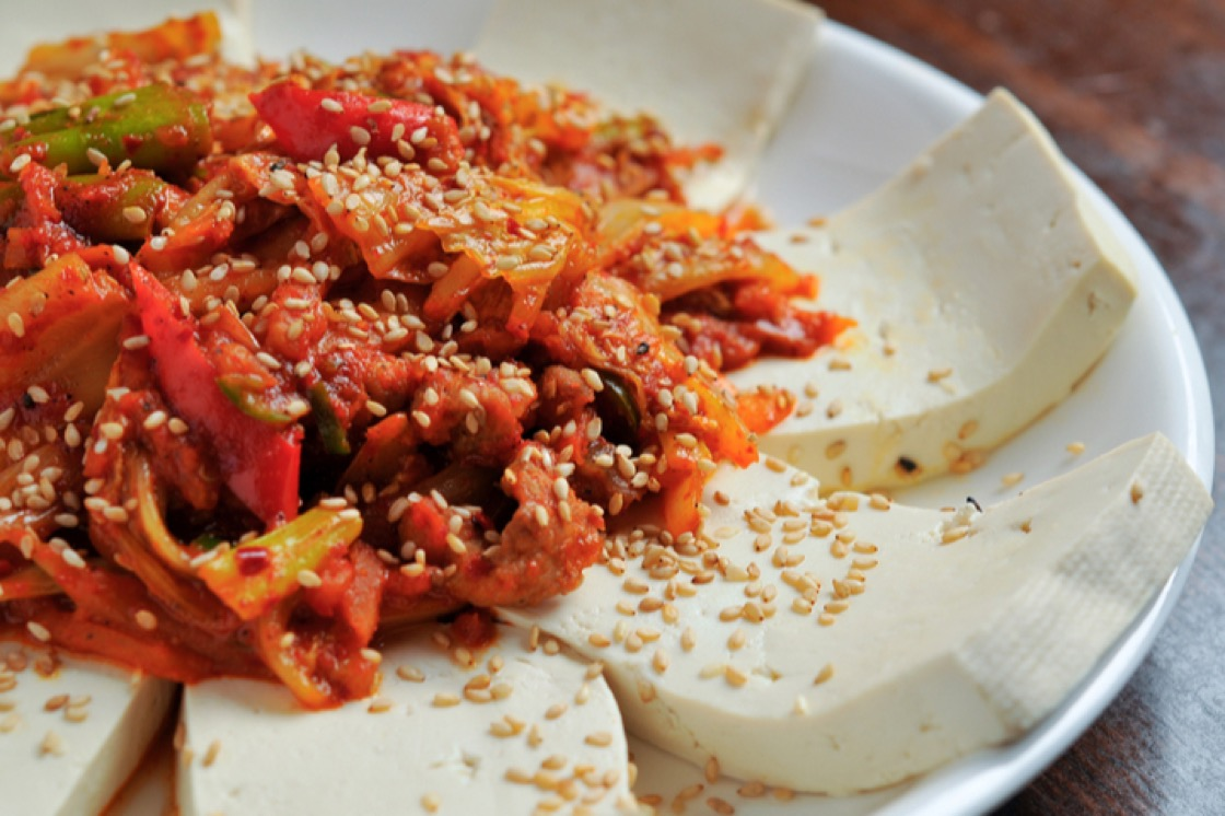 A healthy appetizer of tofu topped with kimchi and white sesame seeds.