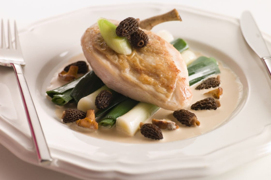 A perfect spring meal: poached chicken breast atop a bed of baby leeks and showered with morel mushroom heads.