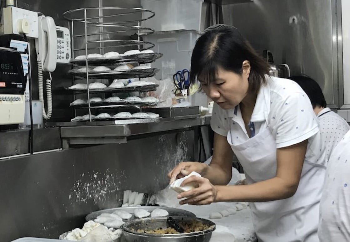 A worker expertly filling and wrapping soon kuehs at Kovan Market & Food Centre's Fatt Soon Kueh.