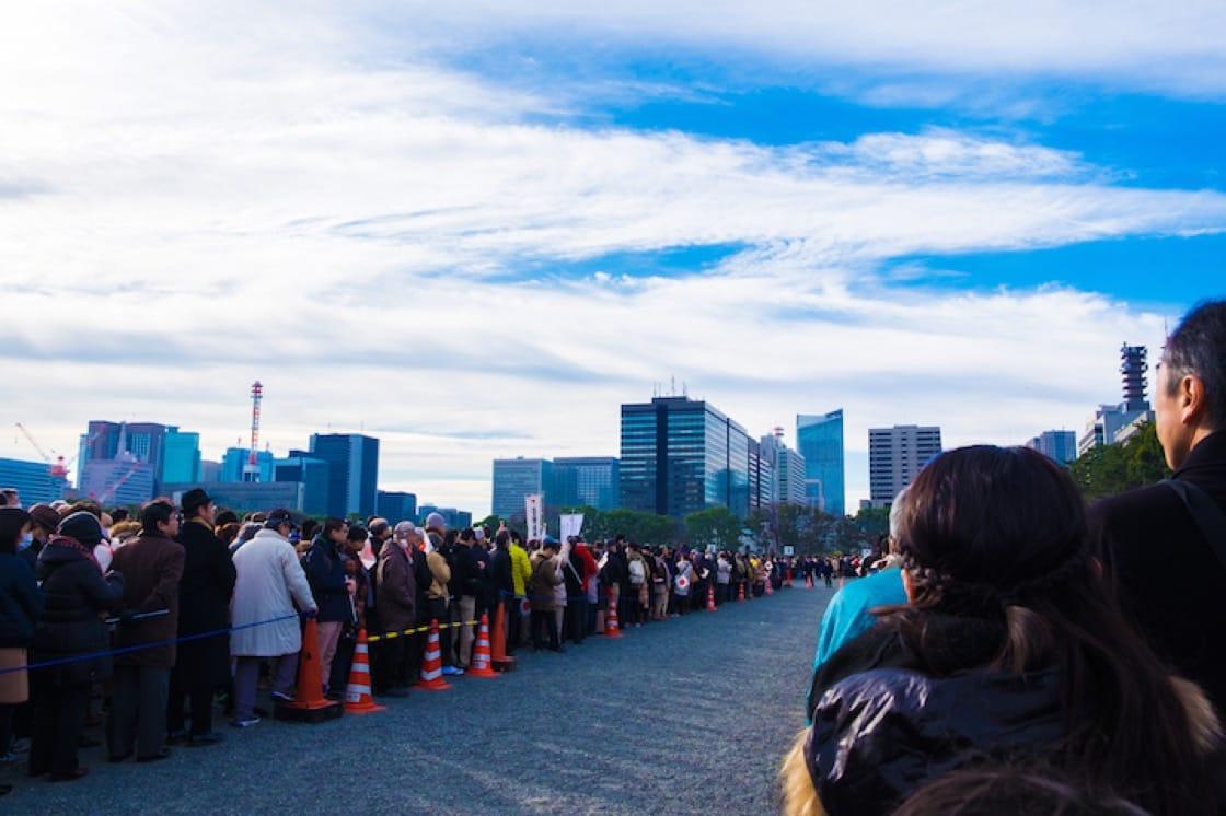 圖為去年 1 月 2 日,日本民眾排隊參與天皇一家現身和民眾打招呼並致辭的情況。