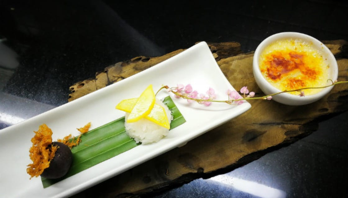 <p><b>Love at First Sight:</b> Chim's version of <b><i> mango sticky rice </b></i> comes with an unconventional look. Slices of yellow mango sit atop the sticky rice and a scoop of coconut ice cream is presented on the side. The chef also adds some flowers and herbs to add a dash of color to the dish.