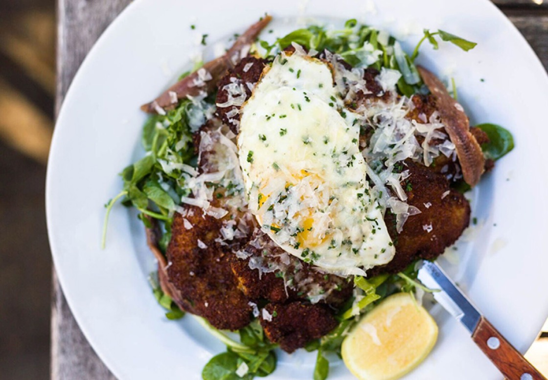 Chicken schnitzel with sunnyside egg, watercress, anchovy, and pecorino di fossa from The Farm on Adderley.