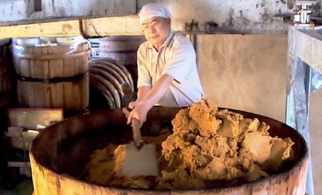 在库房里,河崎父子手持著大木棒,满头大汗搅拌着木桶里的味噌。(拍摄:符祝慧)