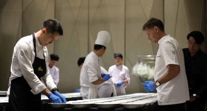 曼谷 Sra Bua by Kiin Kiin 主廚 Chayawee Sutcharitchan(左)與 Henrik Yde-Andersen 為 2018 年米芝蓮曼谷指南的推介會準備美食。