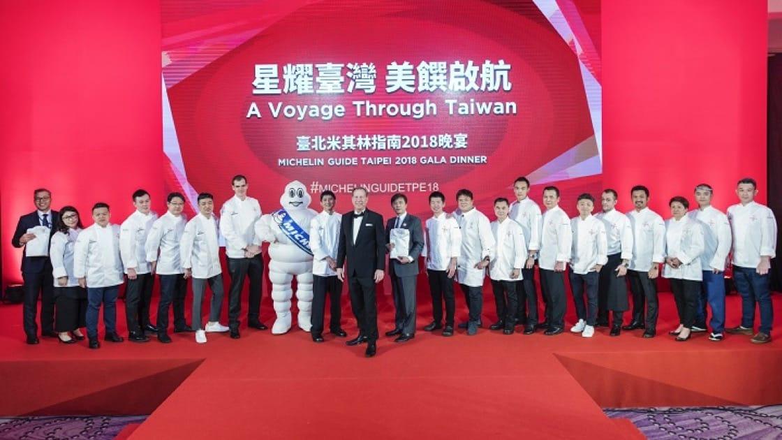 臺北首屆《米其林指南》名單中獲星的 20 家餐廳的主廚與代表,穿上指南為其所訂做的外衣,與《米其林指南》國際總監米高·艾利斯合影。