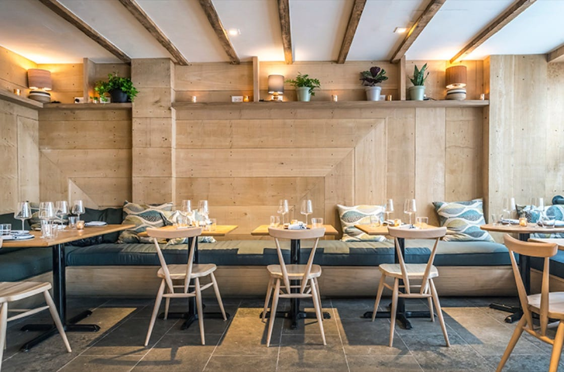 The interior features a combination of French and American white oak walls, spruce beams along the ceiling and elm wood chairs. (Photo courtesy of Ferris.)
