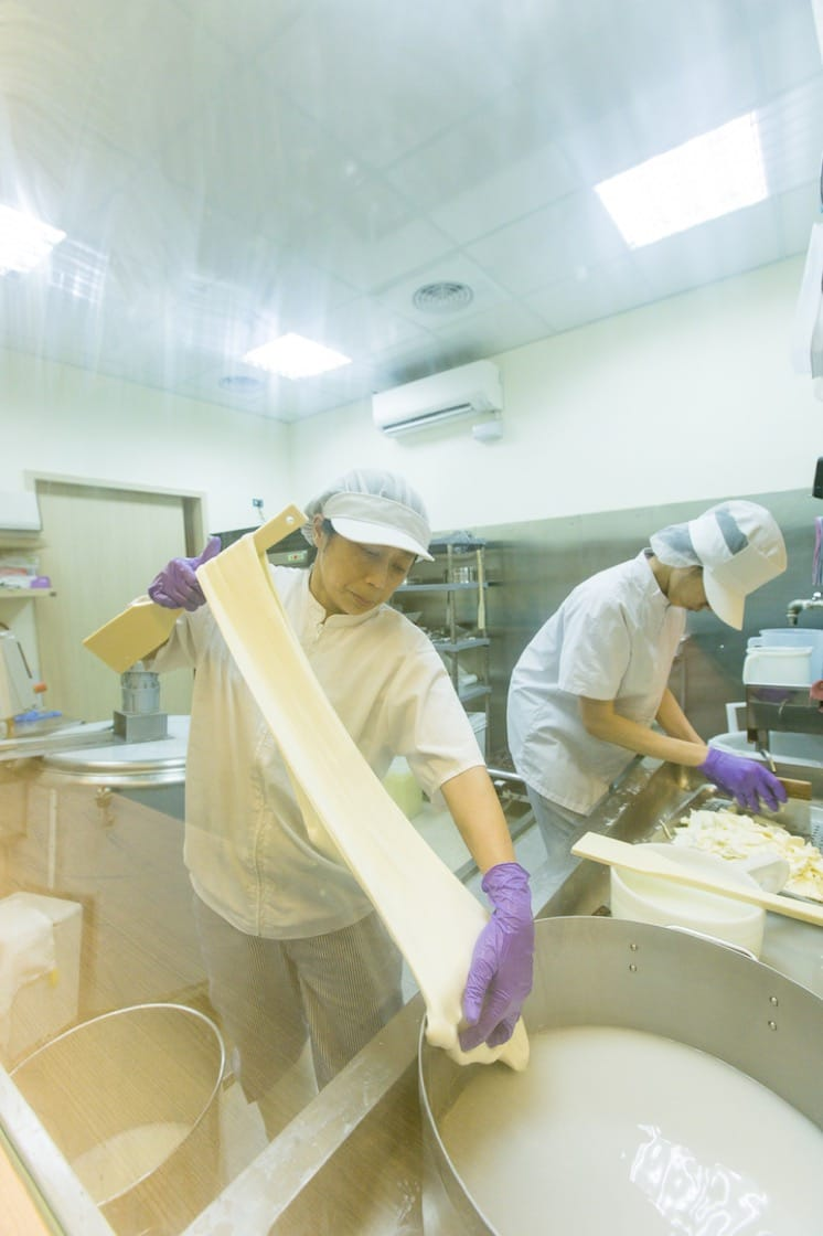 Chen pulls and stretches the curd in hot water of 95°C, kneading and shaping it like dough.