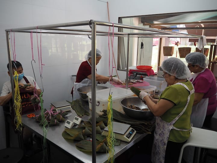 Mr Ryk Chew's parents (on the extreme left) continue to make rice dumplings as manpower is scarce. (Credit: Kenneth Goh)