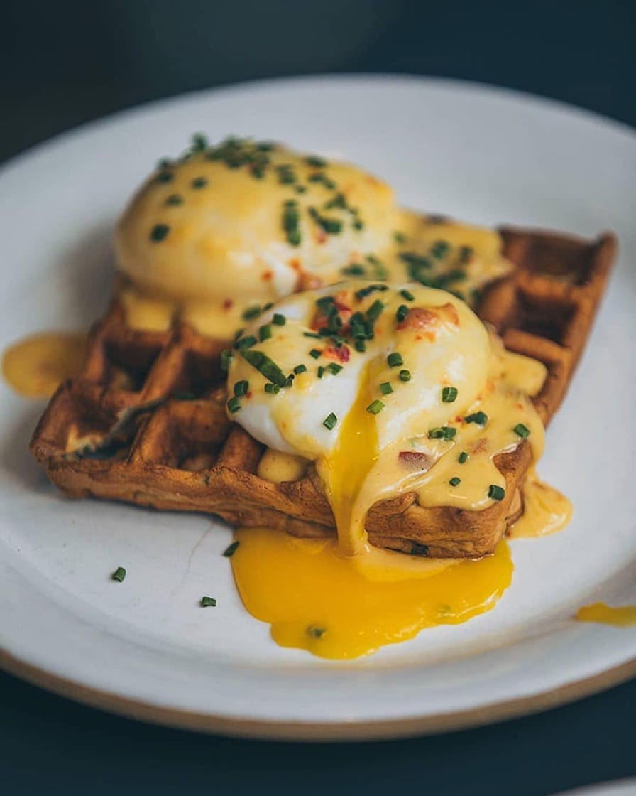 Cheddar waffles and eggs with smoked ham and cherry pepper hollandaise at Loring Place. (Photo by @brunchboys.)