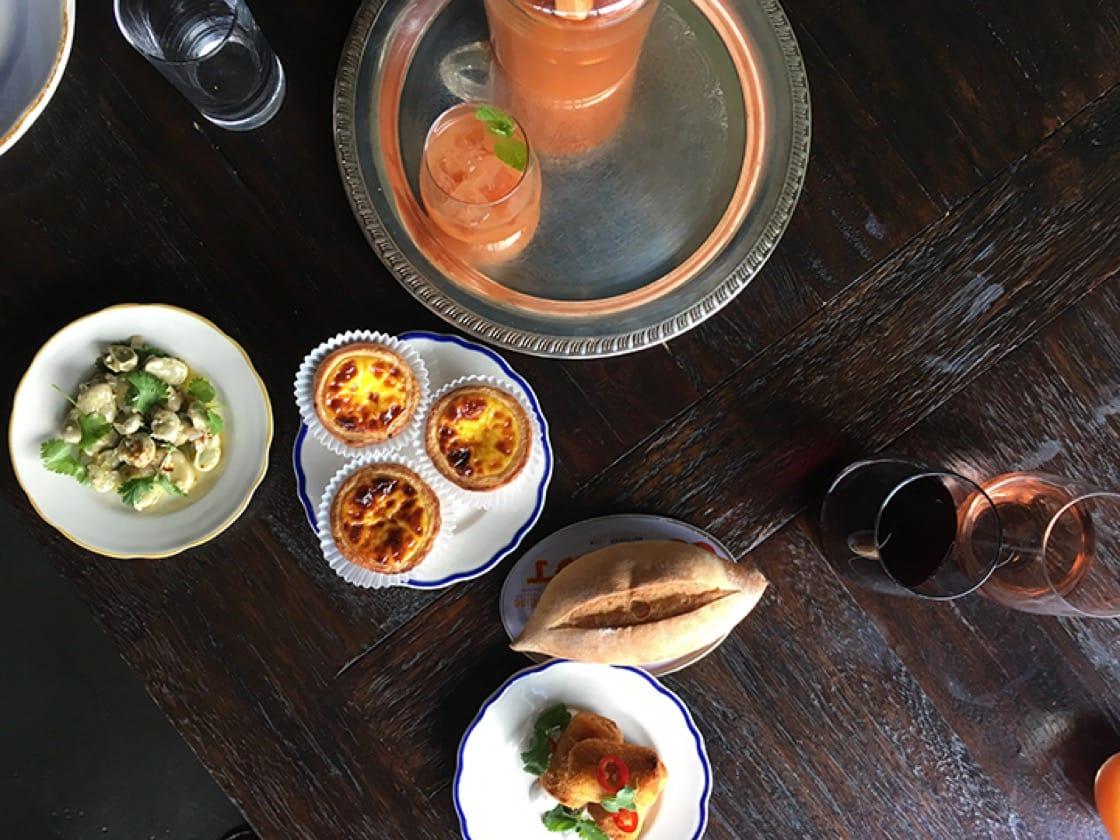 Poncha de Madiera, house-made papo seco (aka, Portuguese bread), fava escabeche, goan choriço croquettes and Portuguese egg tarts at Fat Rice. (Photo by Adrienne Lo.)