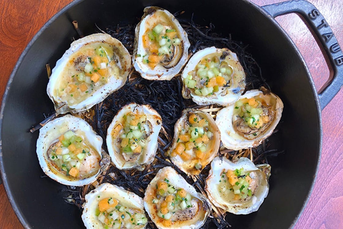 Hay-smoked oysters with melon mignonette and beurre blanc. (Photo by Lani Furbank.)