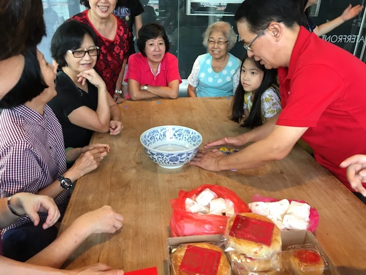 Players of the Mid-Autumn Festival Dice Game take turns to throw six dice, which will determine the size of mooncakes that they can receive. (Credit: Kenneth Goh)