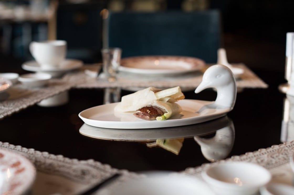 除了先知鴨,頤宮也提供火焰鴨,在桌邊淋酒後燃起火焰後片皮,搭上配料,置於白瓷鴨盤後上桌。(圖:君品提供)