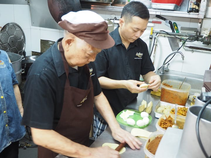 Tham Niap Tong and his son, Bren make and deep-fry the curry puffs in their stall. (Credit: Kenneth Goh)