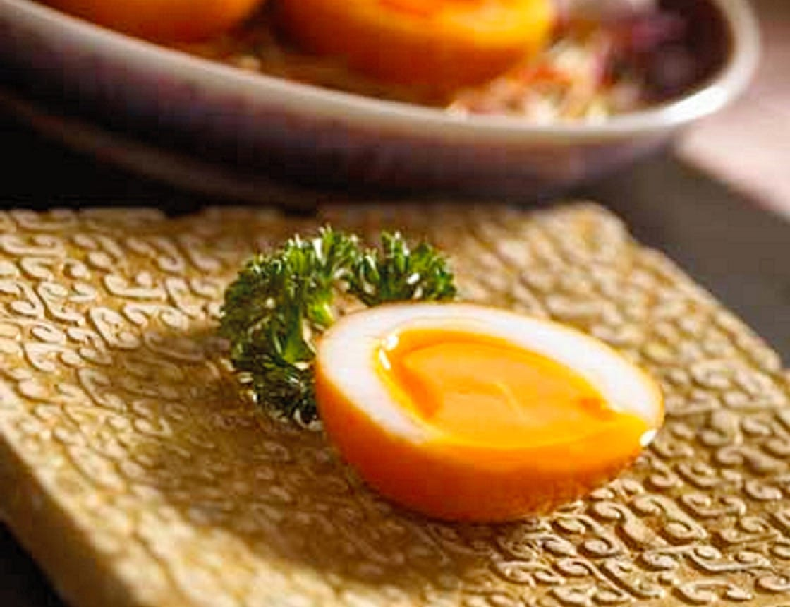 Smoked egg is made first by steeping the egg in master stock to colour its surface. It gets another shade darker through smoking with longjing and other materials. The caramelised skin is a big appeal of the dish. (Pic: Dong Lai Shun)