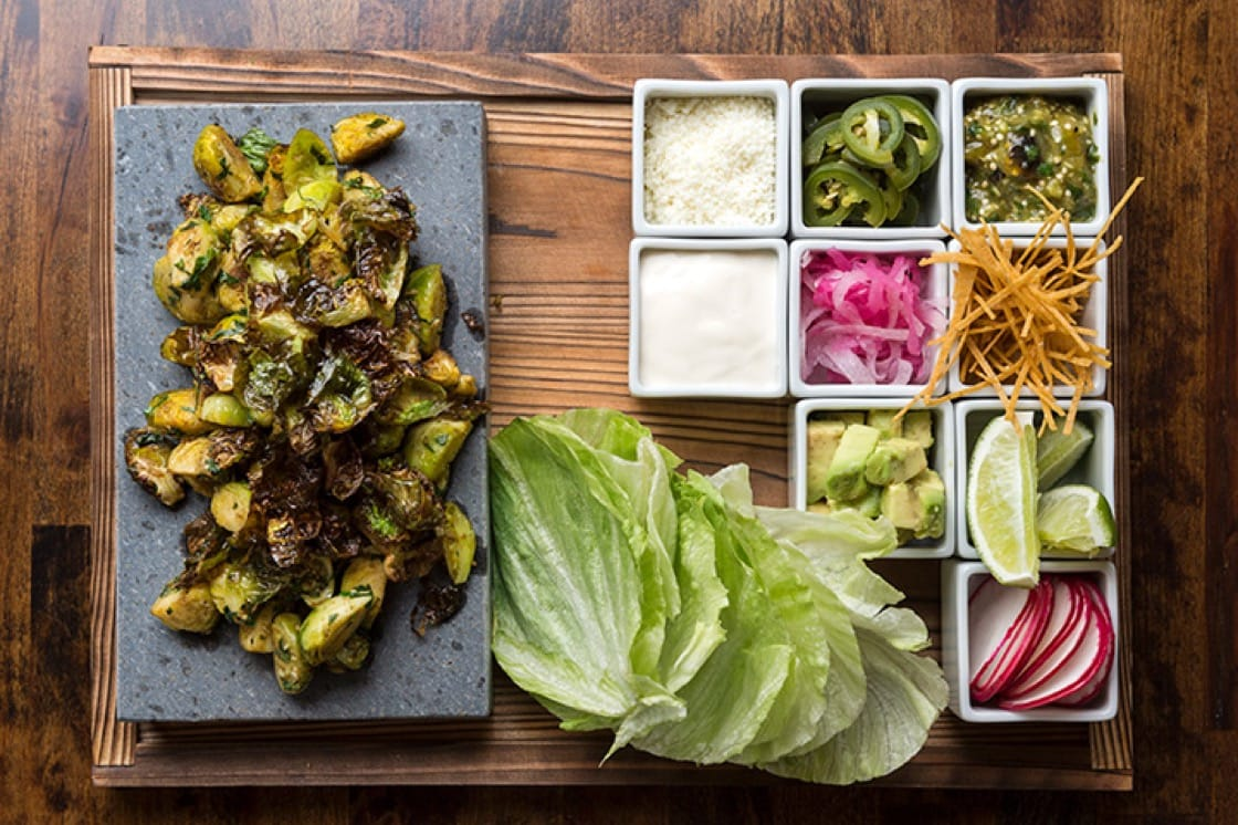 The Brussels sprouts tacos features Brussels sprouts on a sizzling stone with lettuce wrappers and accompaniments. (Photo by Evan Sung.)