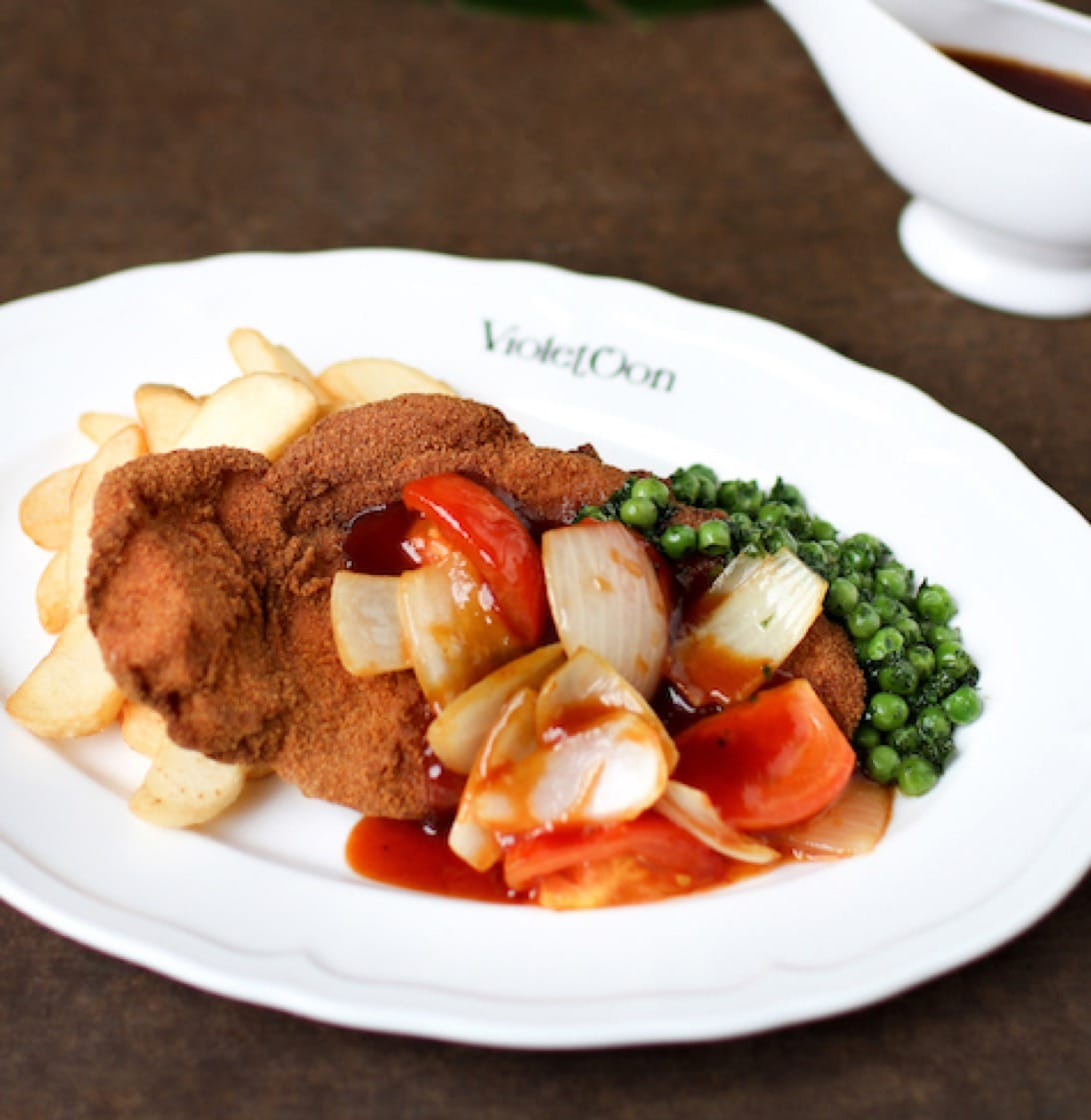 The classic Hainanese pork chop is a golden cream cracker-battered slab of juicy Kurobuta pork loin served with steak cut fries and peas. (Credit: Violet Oon Singapore)
