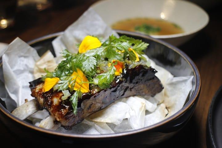 Relæ 與Mume四手餐會菜色,以三種不同的口感豬肉組成,再搭上油封處理的豬腦湯。(陳元慈攝)