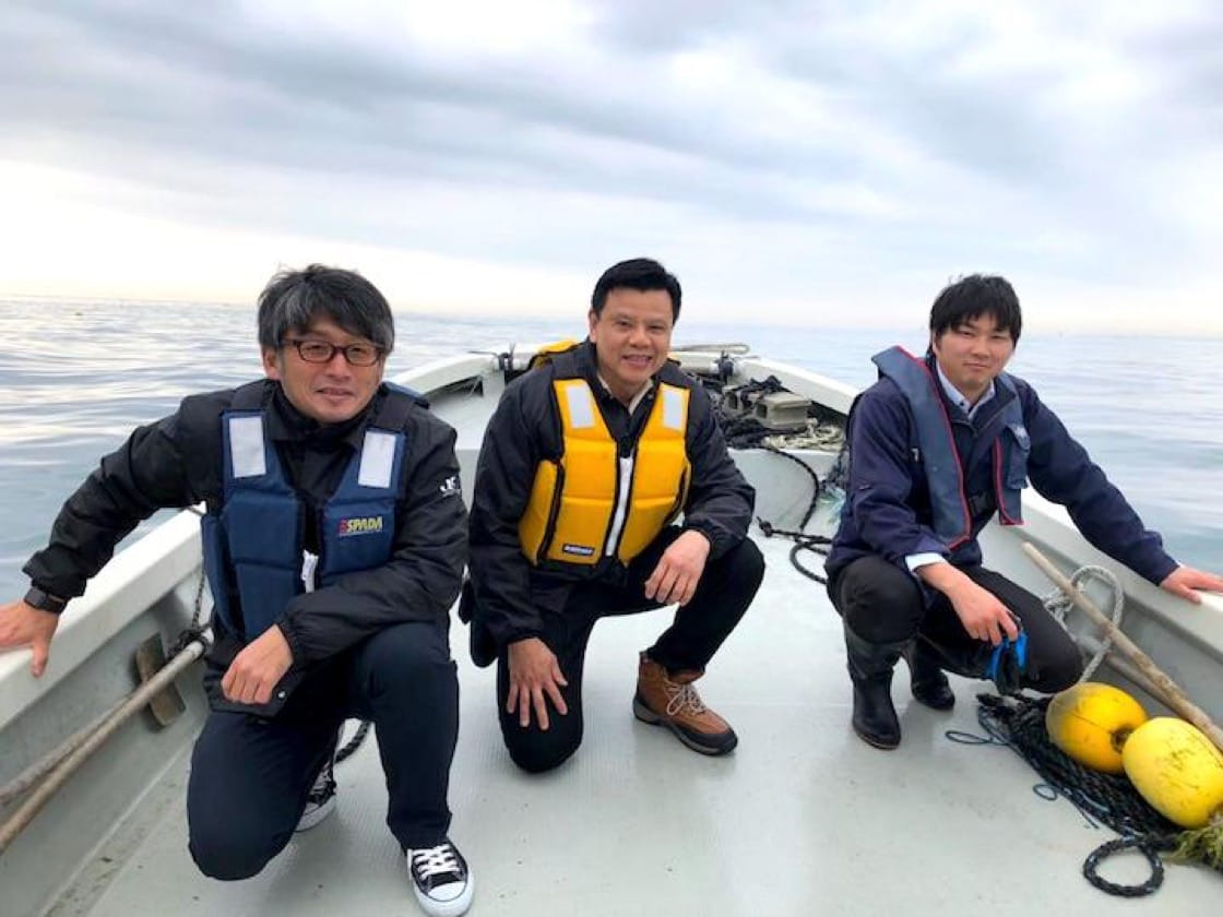 Chi (centre) with his partners from the Japan Fisheries Cooperatives out at sea.