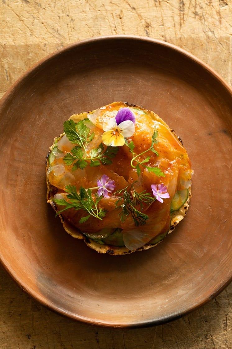 The tostado de pescado is topped with avocado, pumpkin seeds and chile piquin salsa macha.