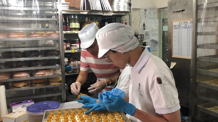 Kitchen staff press down balls of pineapple jam to ensure that they are properly attached to the sides of the pastry dough.