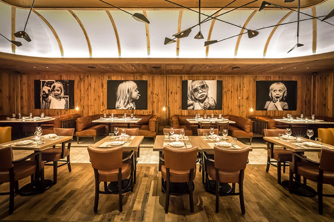 "One of the dining rooms at Leuca is an ""elegant nook fitted out with wood paneling and oversized black-and-white photographs,"" according to inspectors. (Photo by Noah Fecks.)"