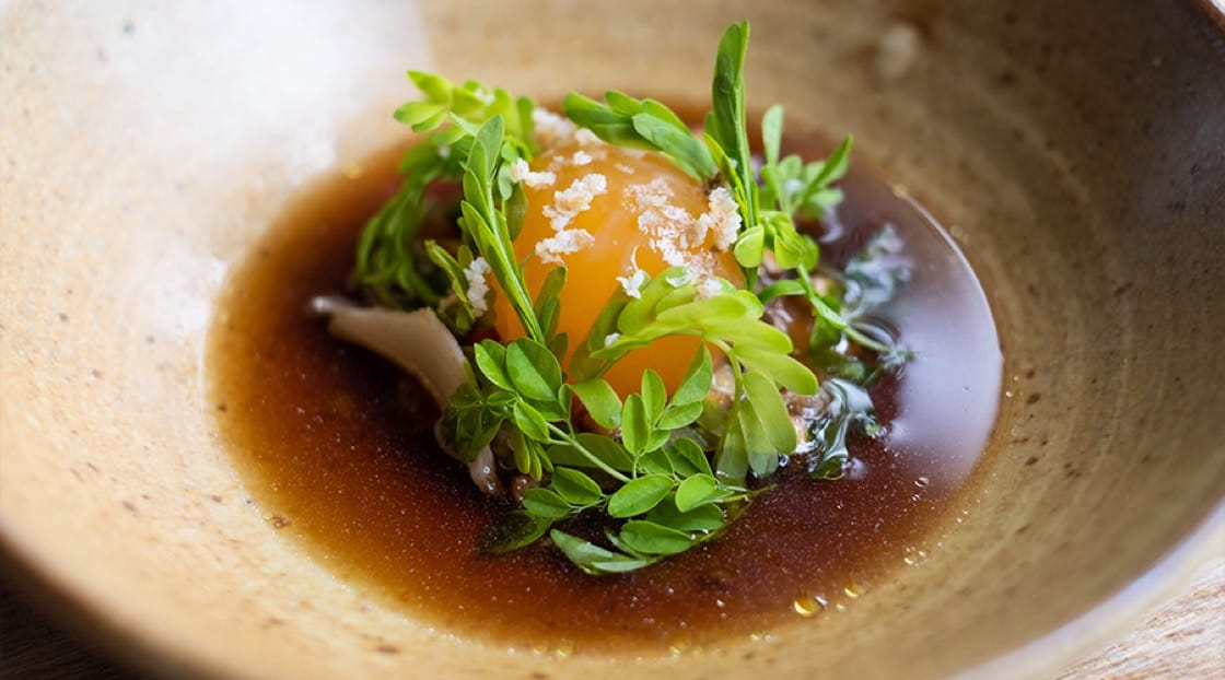 PRU's signature Phuket abalone with pickled duck egg, charred eggplant and wild herbs.