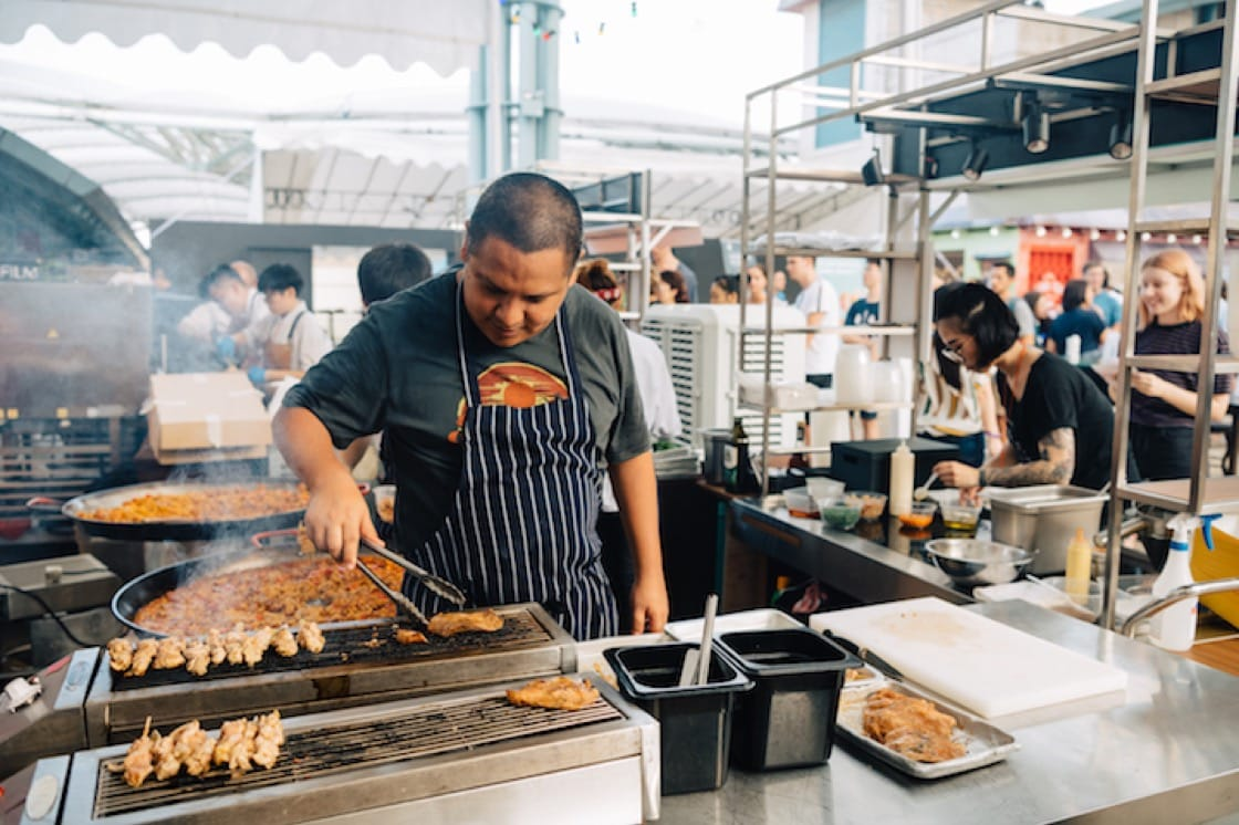 Daniel Chavez, chef-owner of OLA Cocina del Mar cooks Anticuchos (Peruvian marinated chicken skewers) and paella at his stall.