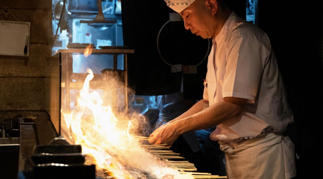 A chef works the yakotri grill in Japan.