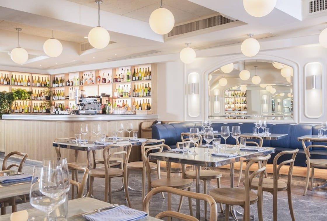 淺色實木家具配水磨石餐桌、藍綠色皮梳化,綴以大鏡子及吊燈,讓食客舒適自在。(圖片:Belon)