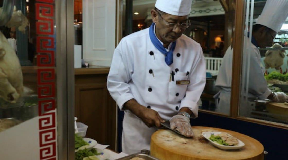 Executive Chef Amnuay plates Ruen Ton's signature dish at the restaurant's dedicated Hainanese chicken rice kiosk.