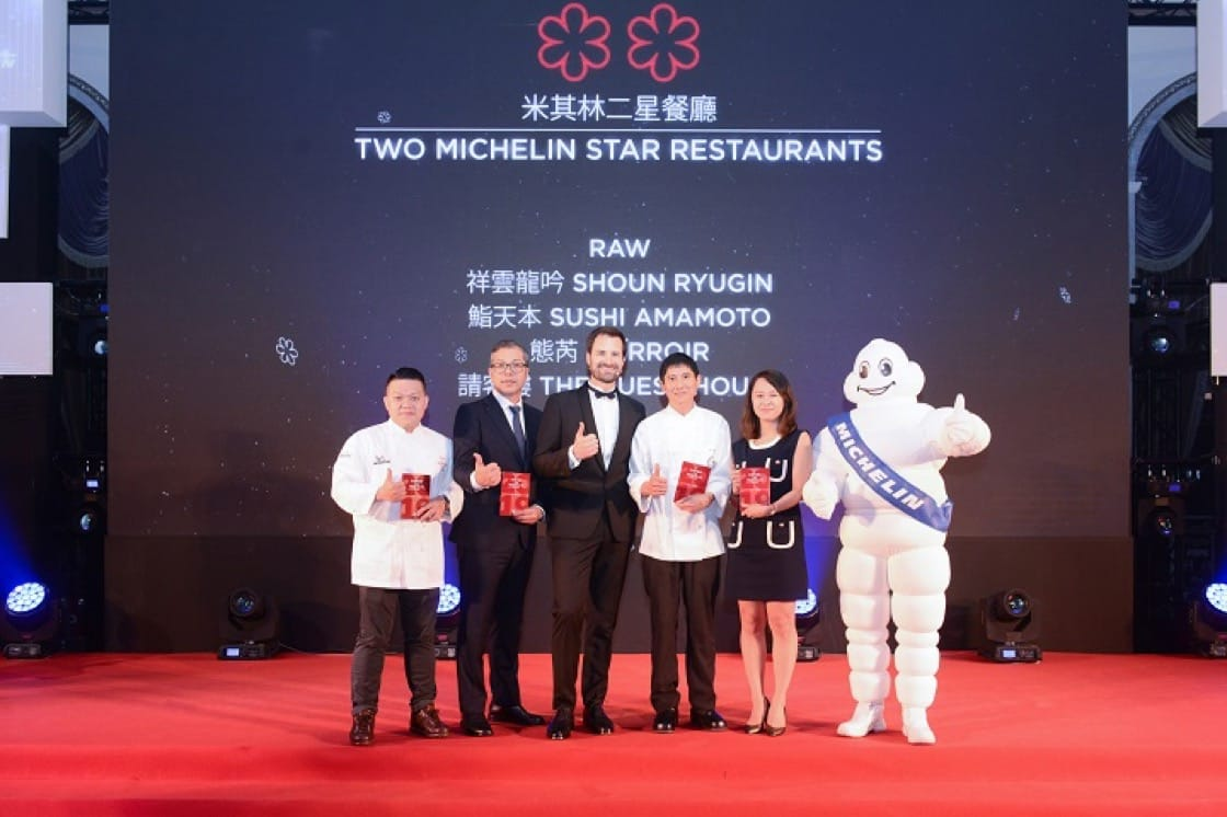 Chefs and representatives from the two-Michelin-starred restaurants pose for a photo with International Director of the MICHELIN Guides Gwendal Poullennec.