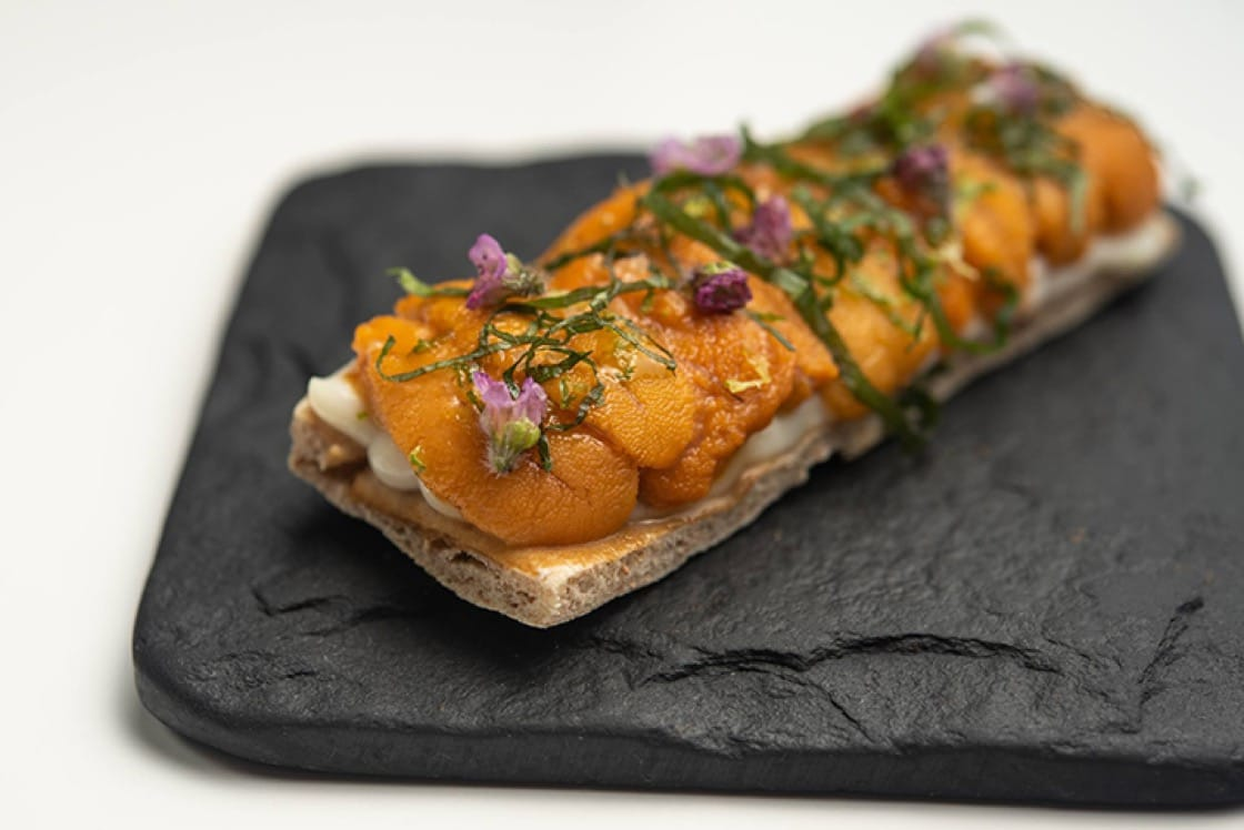 Hokkaido sea urchin toast with cauliflower puree, mustard seed and shiso. (Photo courtesy of Aldea Restaurant/Facebook.)