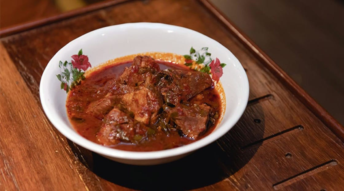Supanniga's signature dish: 'Moo Cha Muang'. A traditional dish from eastern Thailand made with stewed pork belly and slightly sour 'cha muang' leaves in a mild sauce that follows the recipe from Khun Yai.