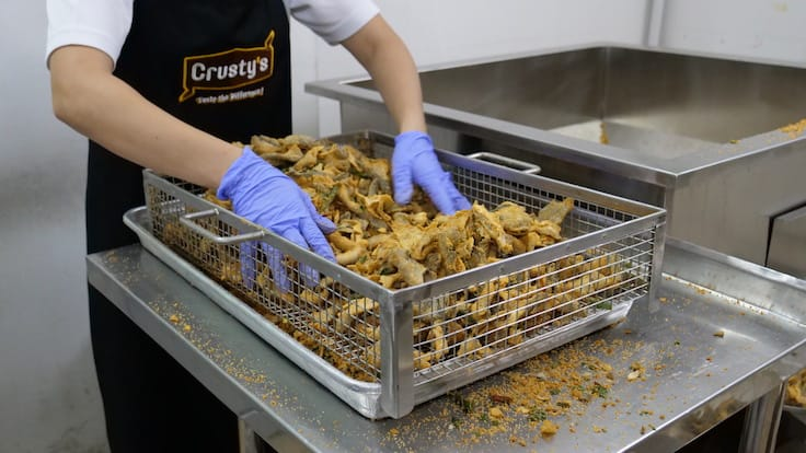 At the factory, every batch of salted egg fish skin is manually checked and excess crumbs are shaken out (Pic: MICHELIN Guide Digital)