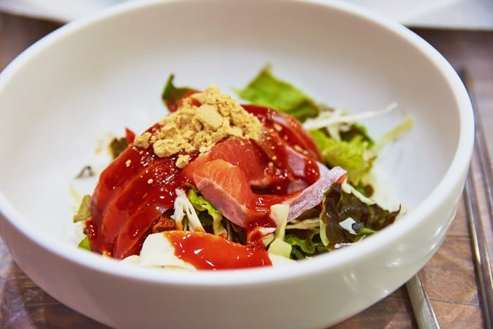 Raw slices of rainbow trout with salad