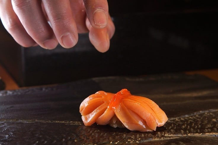 Akagai sushi. After the ark clams are washed, its surface is scrubbed with sea salt before it is blanched in a vinegar mixture and dunked in an ice bath. (Pic: Kitcho)
