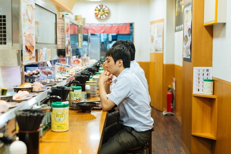 顧客坐在運輸帶外邊,看着不同品種壽司轉到眼前,想吃就可取。(資料圖片)