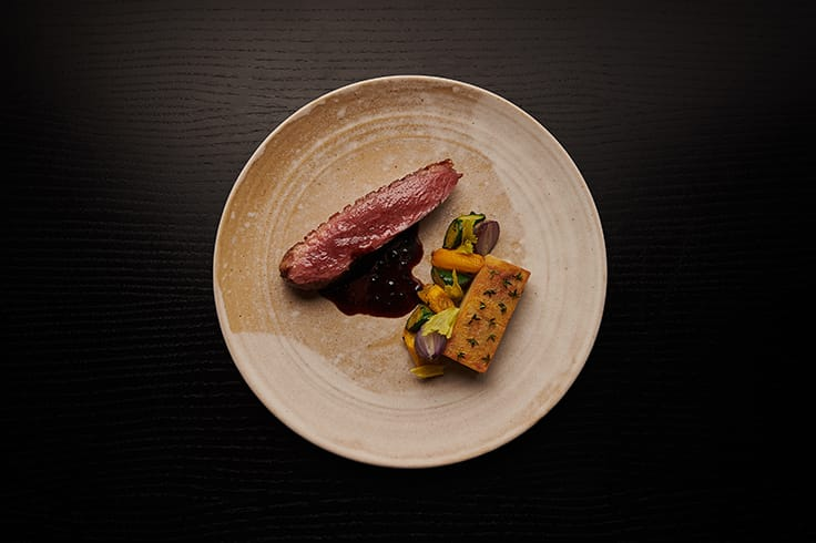 Rohan duck with truffle blueberry duck jus, potato pavé and seasonal vegetables. (Photo by Anthony Tahlier.)