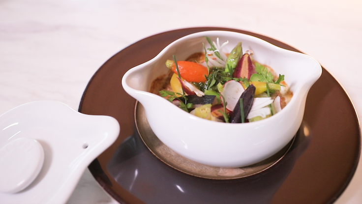 Alain Ducasse's signature cookpot with its seven seasonal vegetables in a white porcelain casserole varies at each of his restaurants all over the world.