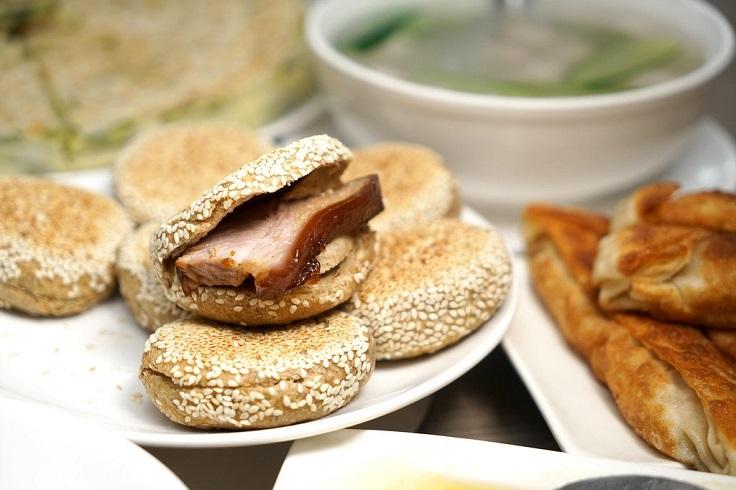 以炭火爐烤的芝麻醬燒餅包招牌醬肉,是很多客人的必點。(圖片:都一處臉書)