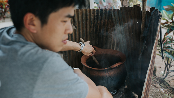Chef Ton making soup in a traditional clay pot.