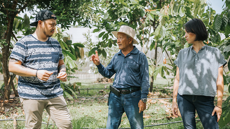 Chef Joe (left) and Chef Saki (right) discussing a plan of action with a northern cacao farmer (center).