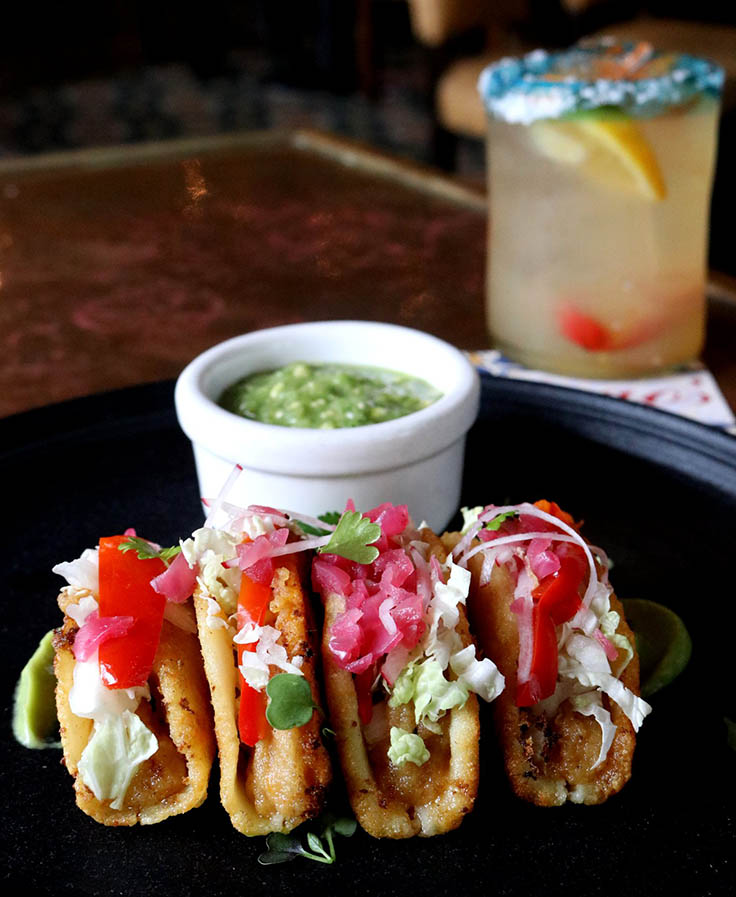 Crispy potato tacos with avocado-tomatillo salsa, pickled jalapeño, Napa cabbage and pickled onions. (Photo courtesy of Hugo's/Facebook.)