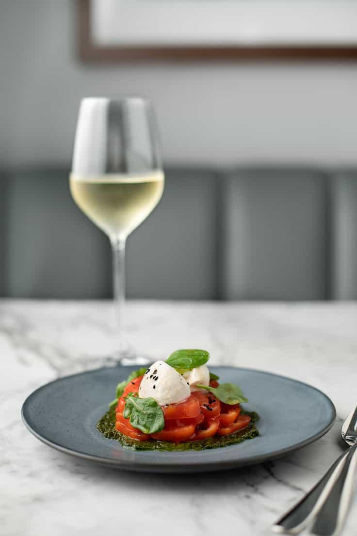 Oxheart tomatoes with basil pesto, burrata and oakleaf at Cornerstone, a new Bib Gourmand recipient in the 2020 selection. (Photo courtesy of Dishtag.)